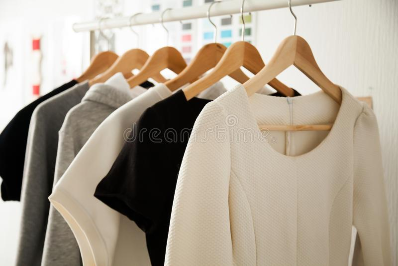 Vrouwenkleren die op hangers hangen die sporen, manierontwerp kleden stock foto