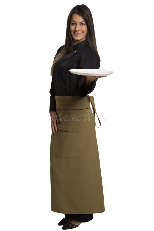 Vrouwenkok of chef-kok die het lege plaat glimlachen dienen stock foto