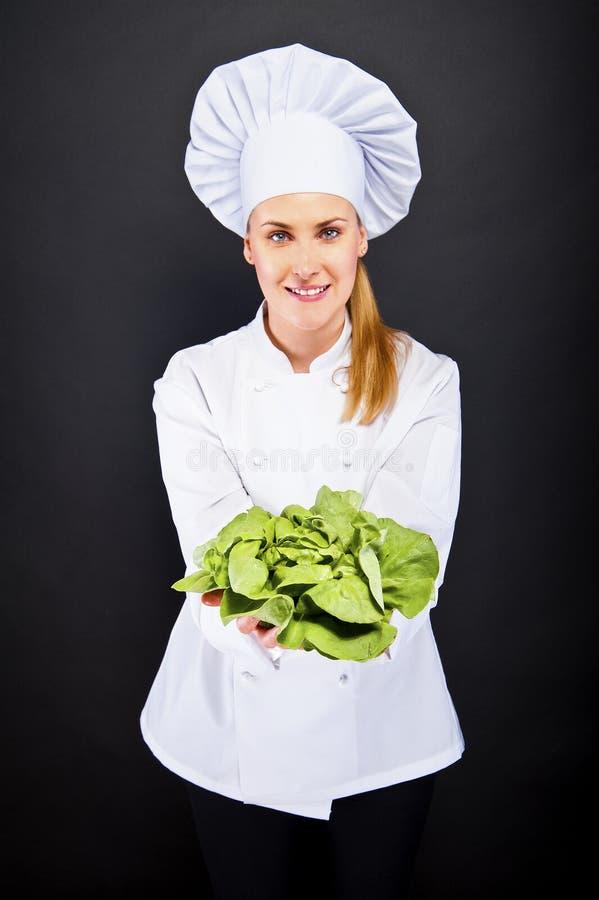 Vrouwenkok met groene salade op een zwarte achtergrond royalty-vrije stock afbeeldingen