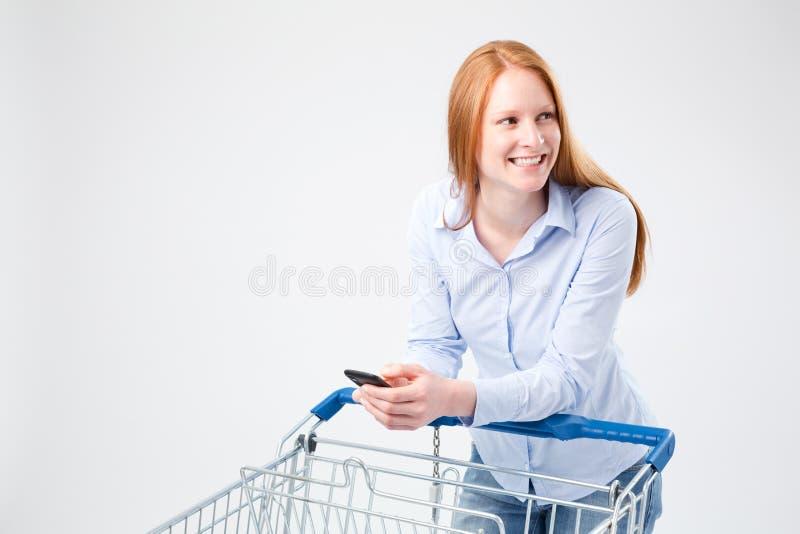Vrouwenkruidenierswinkel die met Smartphone winkelen stock foto's