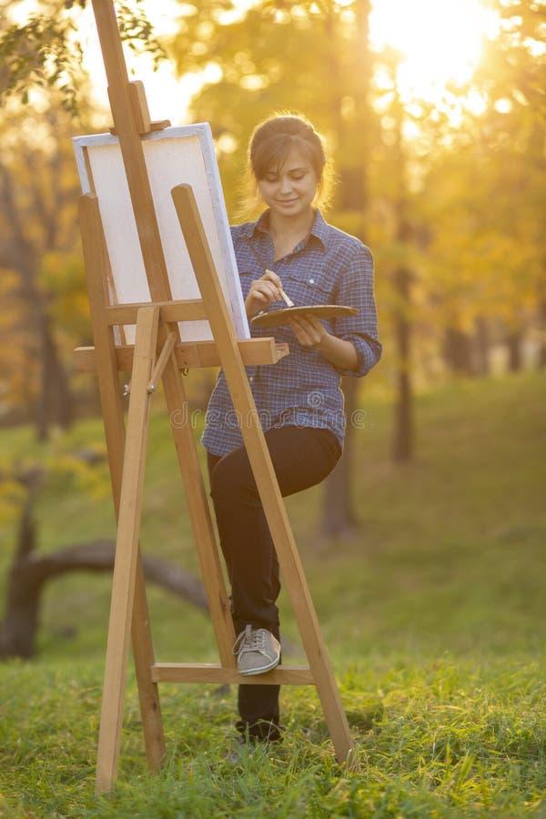 Vrouwenkunstenaar die een beeld op een schildersezel in aard, een meisje met een borstel en een palet, een concept creativiteit e stock foto