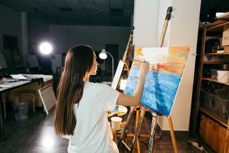 Vrouwenkunstenaar die een beeld op schildersezel met olieverven in haar workshop schilderen stock foto's