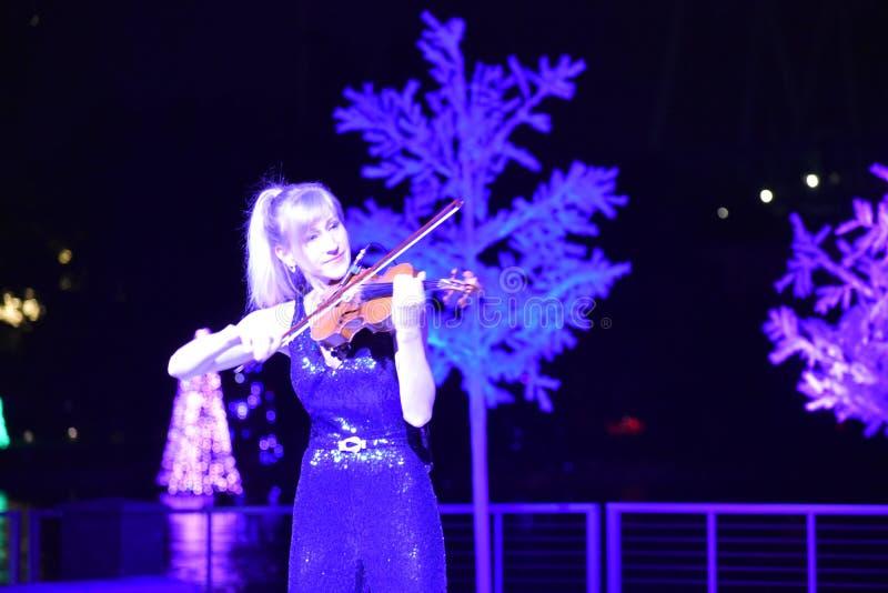 Vrouwenkunstenaar het spelen viool op Kerstmisachtergrond in Internationaal Aandrijvingsgebied stock foto's