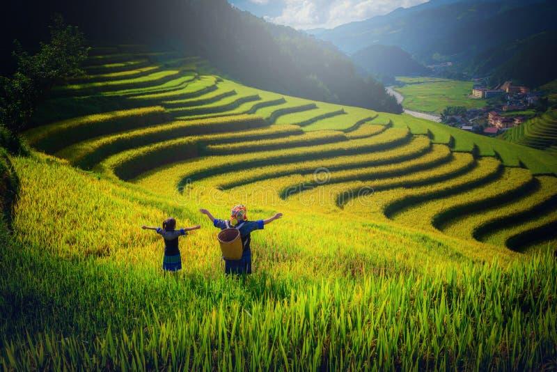 Vrouwenlandbouwer en dochter die wapen op Padievelden terrasvormig opheffen bij royalty-vrije stock fotografie