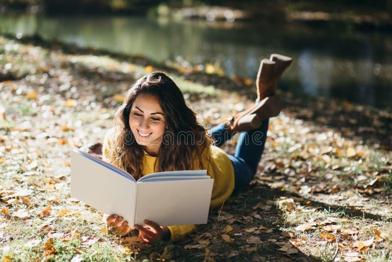 Vrouwenlezing in de herfst openlucht royalty-vrije stock foto's