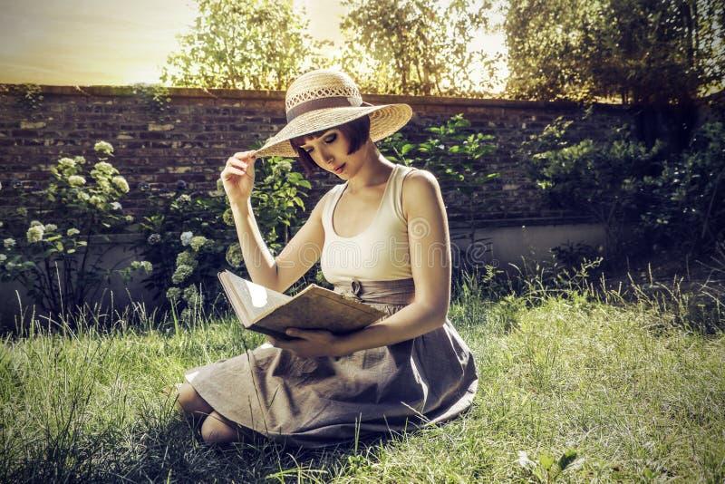 Vrouwenlezing in de tuin royalty-vrije stock afbeeldingen