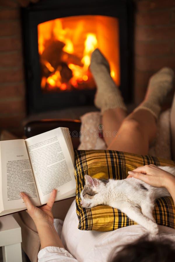 Vrouwenlezing door de brand die - met haar kat ontspannen royalty-vrije stock foto