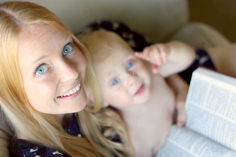 Vrouwenlezing met Baby op haar Overlapping royalty-vrije stock afbeeldingen