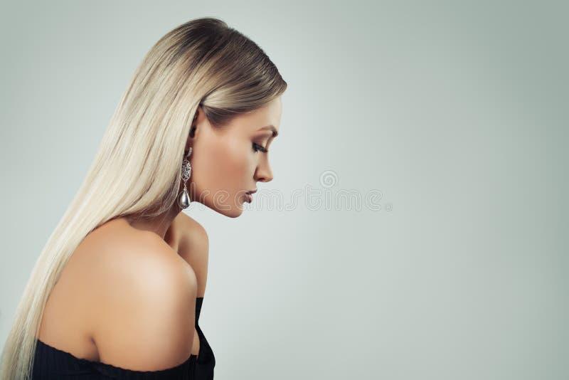 Vrouwenmannequin met Blondehaar, Make-up en Zwarte Parelsoorringen op Achtergrond met Exemplaarruimte, Profiel royalty-vrije stock foto