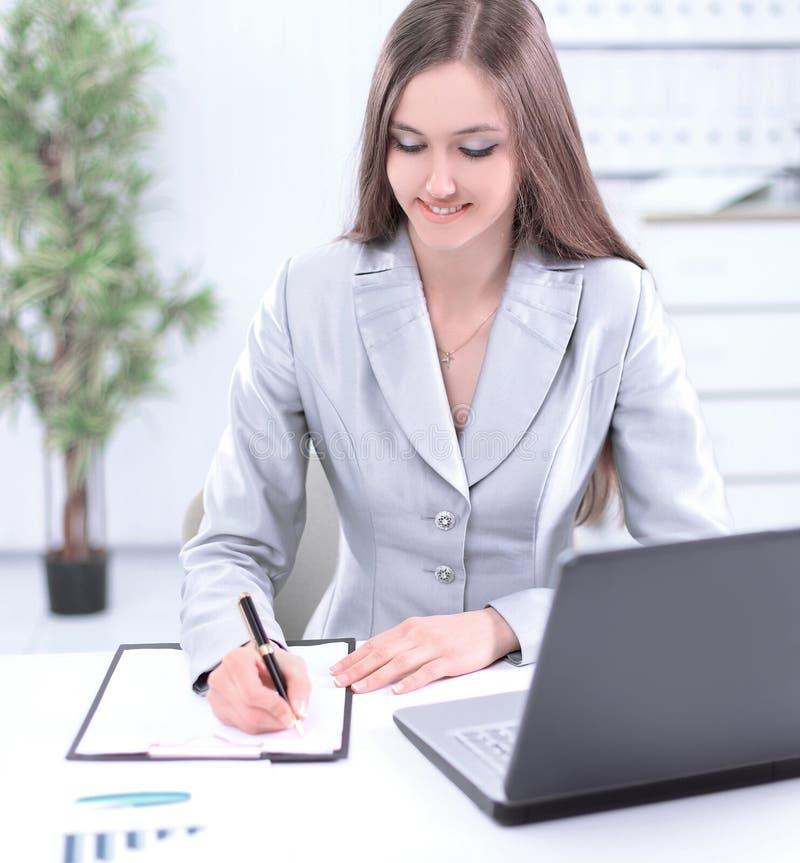 Vrouwenmedewerker die een verslag op een blad van document maken royalty-vrije stock foto