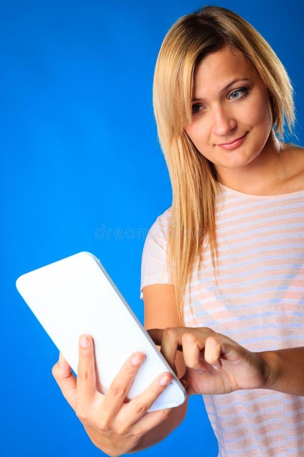 Vrouwenmeisje die de e-lezer van de tablet touchpad lezing eBook op blauw met behulp van royalty-vrije stock fotografie