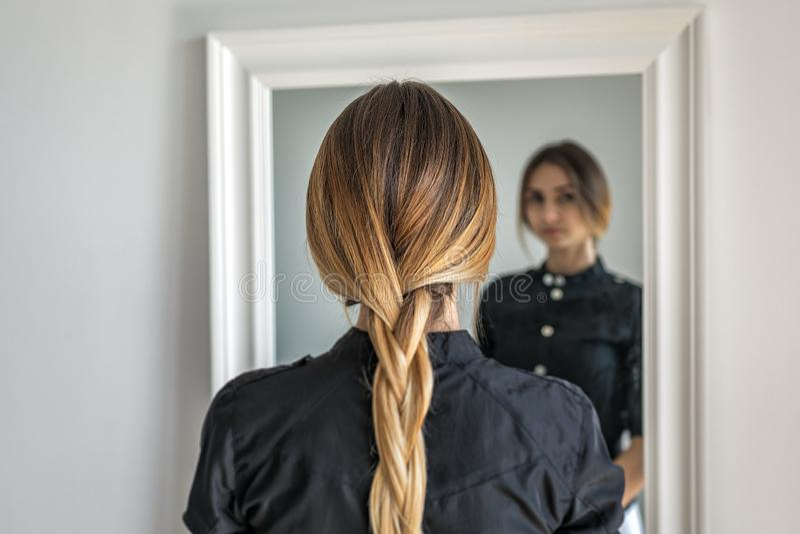 Vrouwenmeisje met ombrekapsel in vlecht voor spiegel stock foto