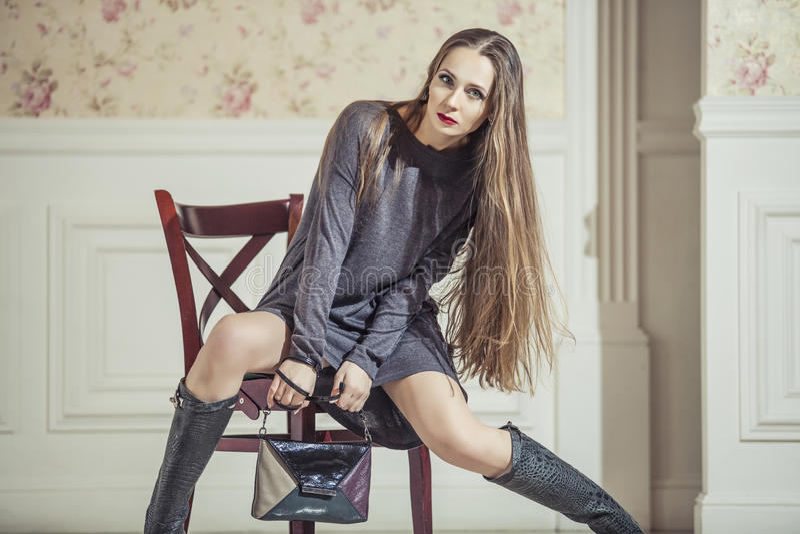 Vrouwenmodel in kleding met modieuze laarzen en heldere rode lippen royalty-vrije stock foto