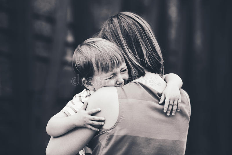 Vrouwenmoeder die haar troosten die weinig zoon van de peuterjongen schreeuwen stock foto