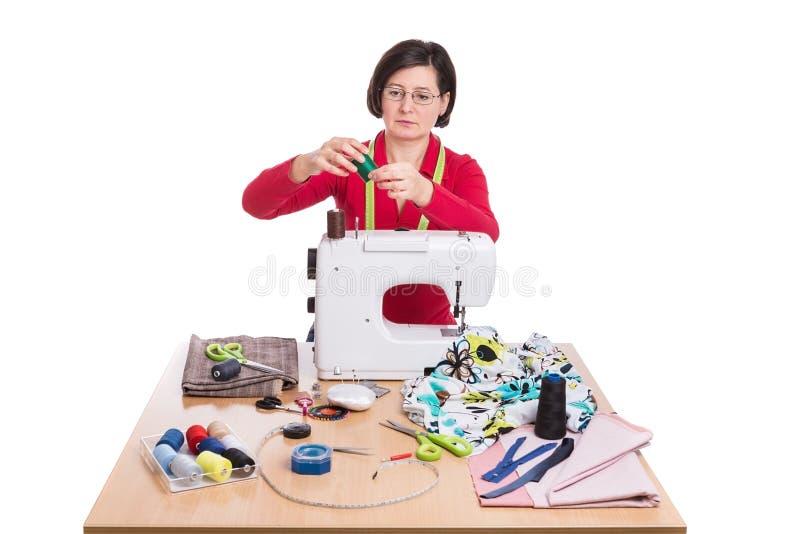 Vrouwennaaister bij de naaimachine stock afbeelding