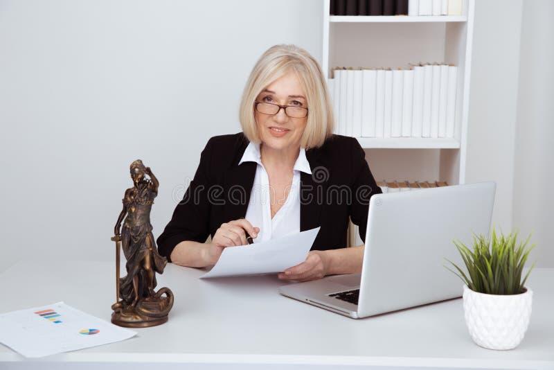 Vrouwennotaris bij het bureau voor computer met documenten Standbeeld van rechtvaardigheid stock foto