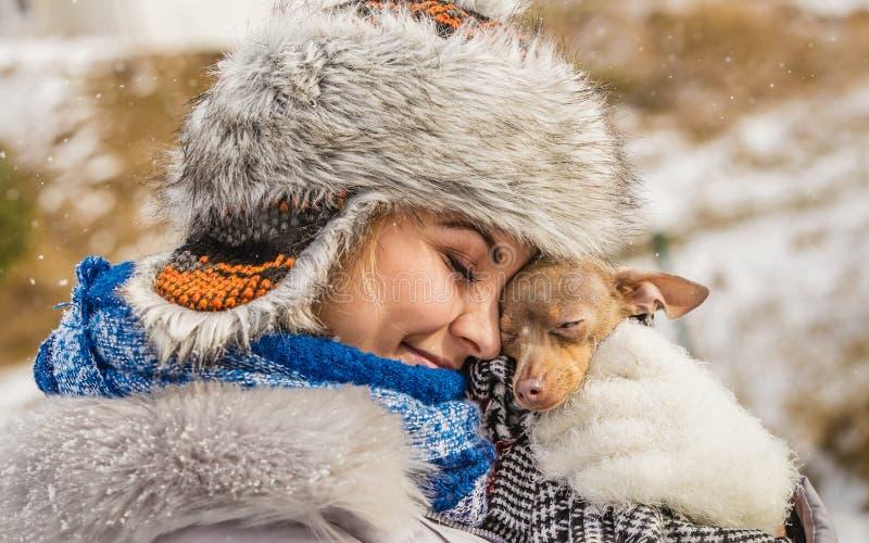 Vrouwenomhelzing die haar verwarmen weinig hond in de winter royalty-vrije stock foto's