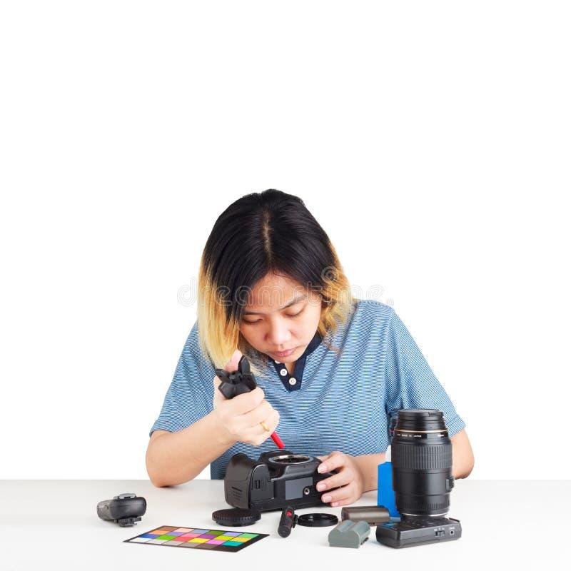 Vrouwenonderhoud een DSLR-Camera met stof brower in haar hand royalty-vrije stock foto's