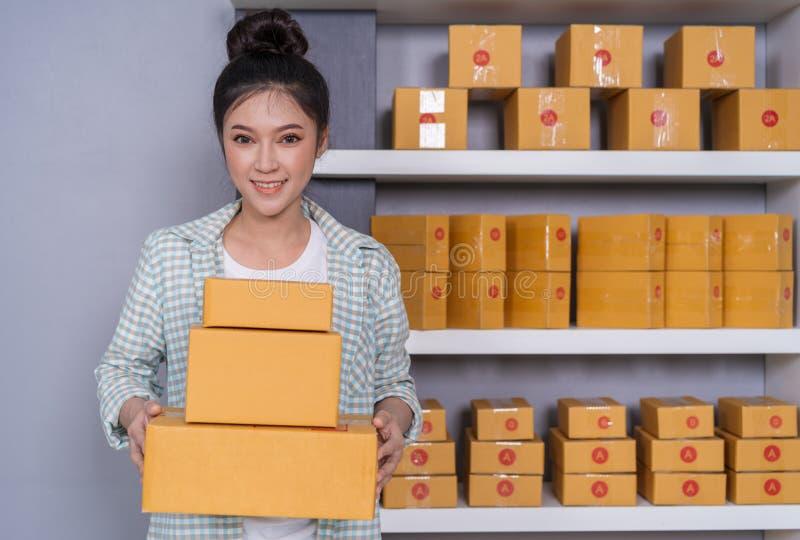 Vrouwenondernemer die met pakketdozen in haar eigen baan onl winkelen stock foto