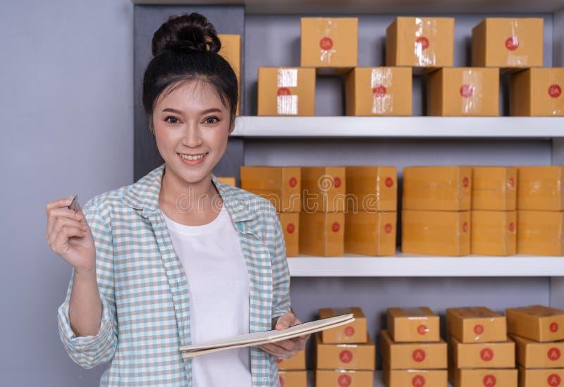 Vrouwenondernemer die met pakketdozen in haar eigen baan onl winkelen stock afbeeldingen
