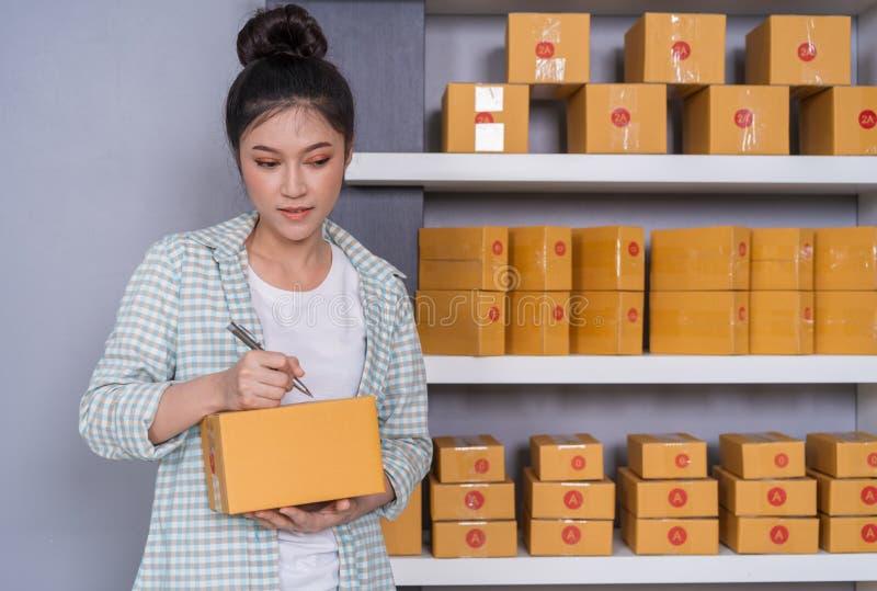 Vrouwenondernemer die op pakketdoos schrijven, online zaken, prepa stock fotografie
