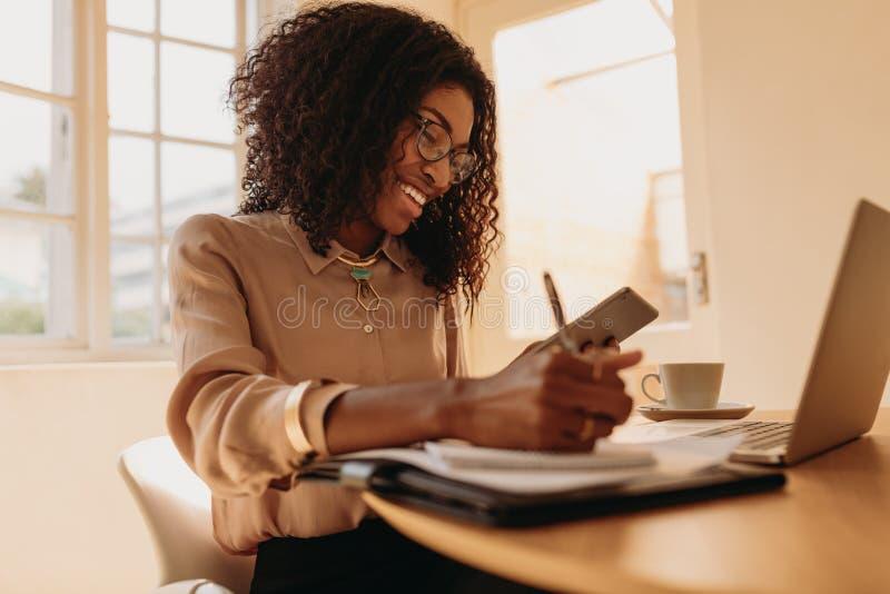 Vrouwenondernemer die van huis aan laptop werken stock afbeeldingen