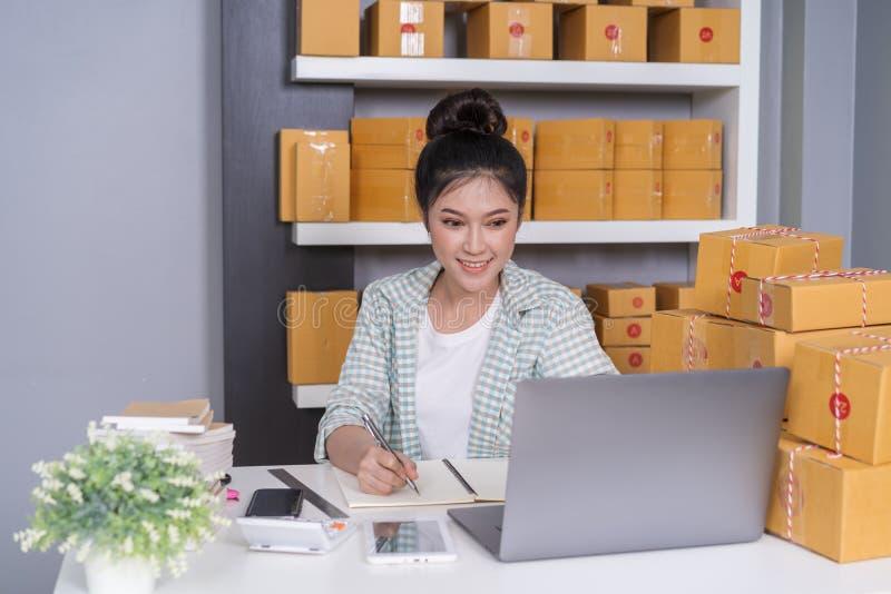 vrouwenondernemer het controleren en het schrijven de orde met karton, het MKB-zaken treffen online binnen voor levering voorbere royalty-vrije stock foto's