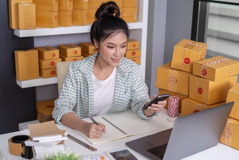 vrouwenondernemer het controleren en het schrijven de orde met karton, het MKB-zaken treffen online binnen voor levering voorbere stock afbeelding