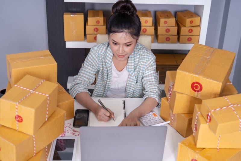 vrouwenondernemer het controleren en het schrijven de orde met karton, het MKB-zaken treffen online binnen voor levering voorbere stock foto