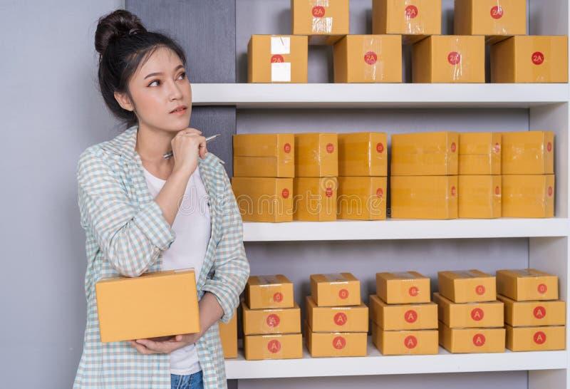 vrouwenondernemer het denken met pakketdoos, online zaken, treft vóór levering voorbereidingen stock afbeelding