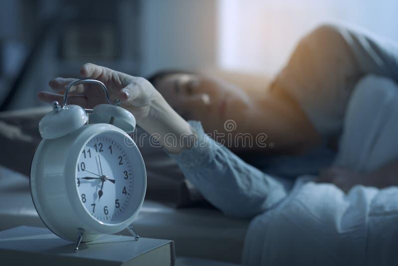 Vrouwenontwaken in de ochtend en de wekker royalty-vrije stock afbeeldingen
