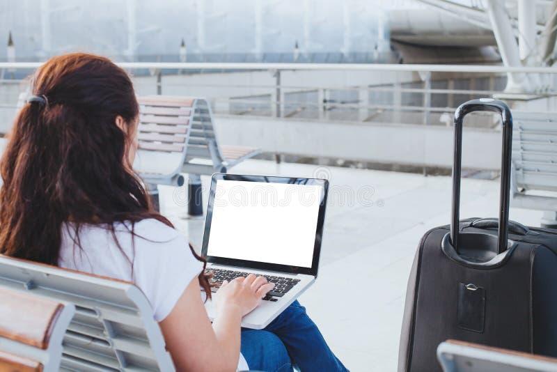 Vrouwenpassagier die laptop computer in de luchthaven, online beleggend of Webcontrole met behulp van royalty-vrije stock afbeelding