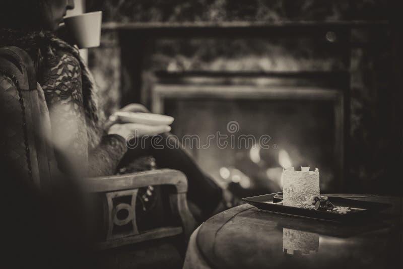 Vrouwenplaatsing dichtbij open haard en het drinken kop van koffie en het eten van mooi de winterdessert met chocolade, productfo stock afbeeldingen
