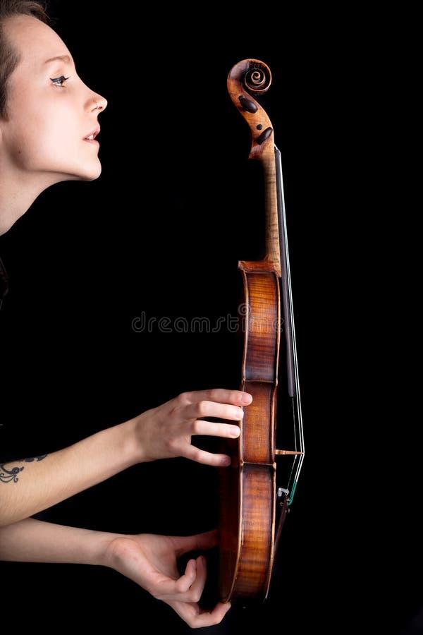 Vrouwenprofiel en viool op zwarte achtergrond royalty-vrije stock foto
