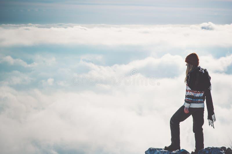 Vrouwenreiziger alleen op klip over wolken stock afbeelding
