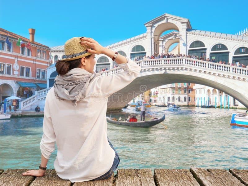 Vrouwenreiziger die in hoed de zomer van tijd, Rialto-Brug op de achtergrond genieten, Venetië royalty-vrije stock afbeelding