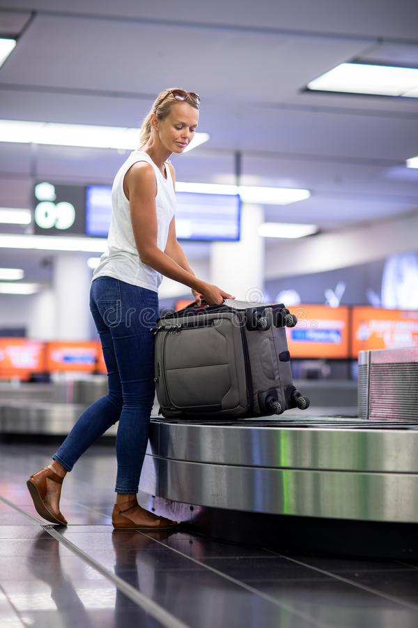 Vrouwenreiziger die koffer van bagageband opnemen royalty-vrije stock foto's