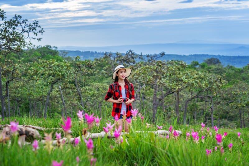Vrouwenreiziger die met rugzak bij Krachiew-bloemgebied genieten van, Thailand reis concept stock foto's