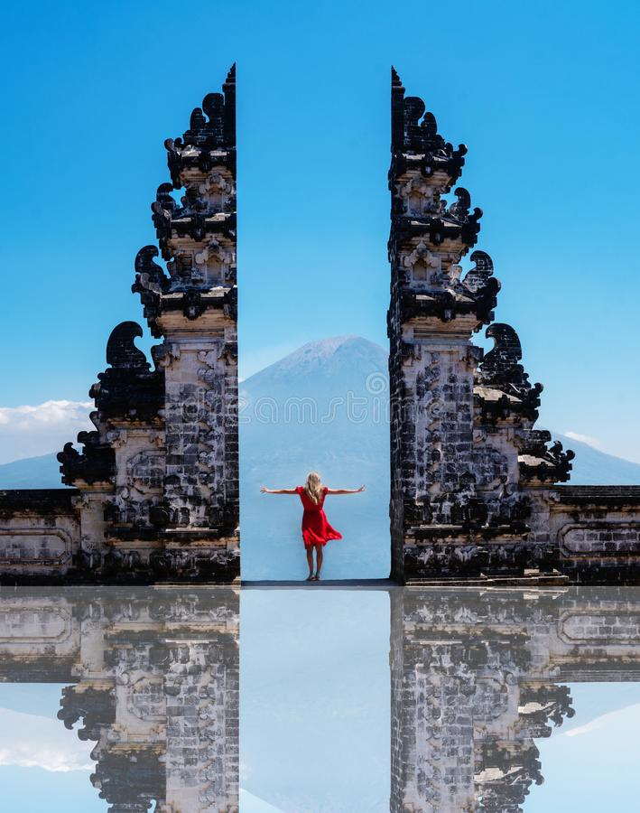 Vrouwenreiziger die zich bij de oude poorten van Pura Luhur Lempuyang-de Poorten van tempelaka van Hemel in Bali bevinden royalty-vrije stock fotografie