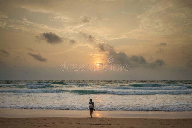 Vrouwenreiziger die zich in de afstand op het strand bevinden en de zonsondergang bekijken stock afbeeldingen