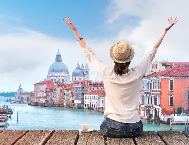 Vrouwenreiziger in hoed met opgeheven wapens en kop van koffie op brug in Venetië royalty-vrije stock afbeeldingen