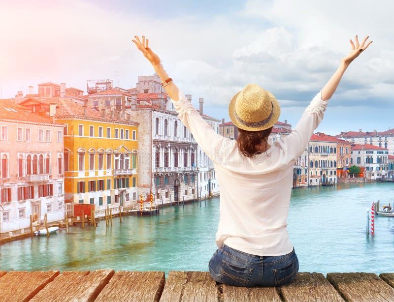 Vrouwenreiziger in hoed met wapens op brug in Venetië worden opgeheven dat royalty-vrije stock afbeeldingen