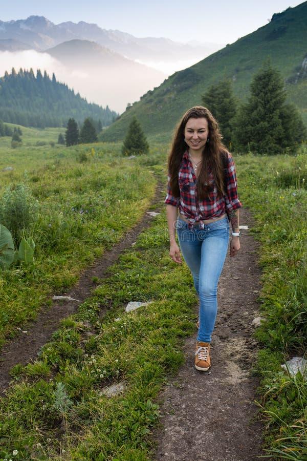Vrouwenreiziger met de hoed van de rugzakholding en het bekijken verbazend bergen en bos, het concept van de zwerflustreis, ruimt royalty-vrije stock afbeeldingen