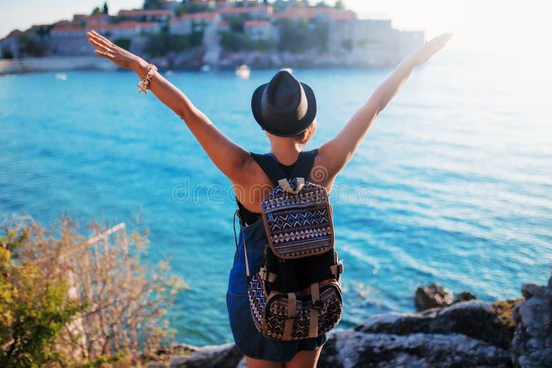 Vrouwenreiziger met rugzak dichtbij Sveti Stefan bij Adriatische overzees stock foto's