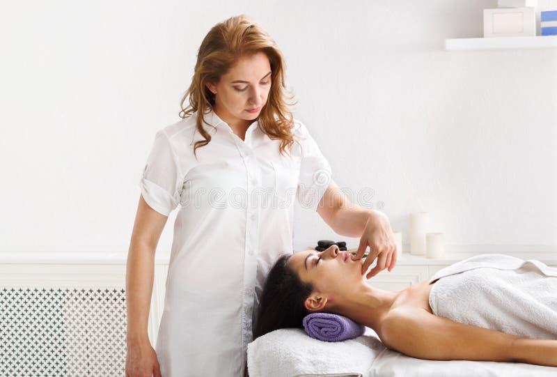 Vrouwenschoonheidsspecialist de arts maakt hoofdmassage in het centrum van kuuroordwellness royalty-vrije stock afbeelding
