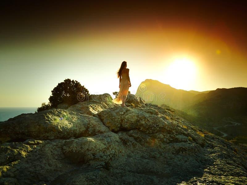 Vrouwensilhouet bij zonsondergang in bergen stock afbeeldingen
