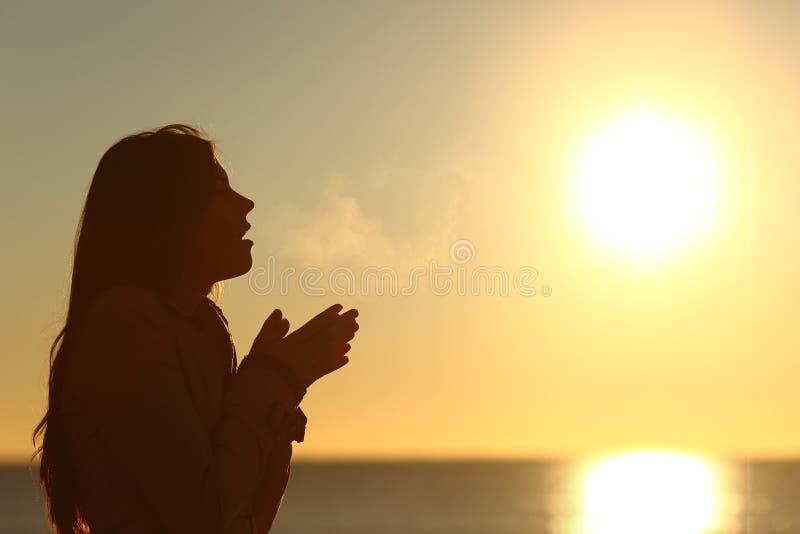 Vrouwensilhouet die in de koude winter ademen stock afbeeldingen