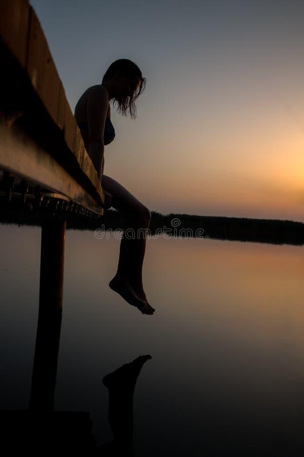 Vrouwensilhouet in zonsondergang op het houten dok royalty-vrije stock afbeeldingen