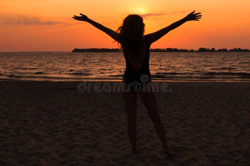 Vrouwensilhouet in zwempak met stromend haar, opgeheven handen en status op strand dichtbij overzees stock afbeelding