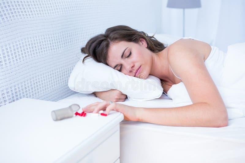 Vrouwenslaap in bed door gemorste fles van pillen op lijst stock foto's